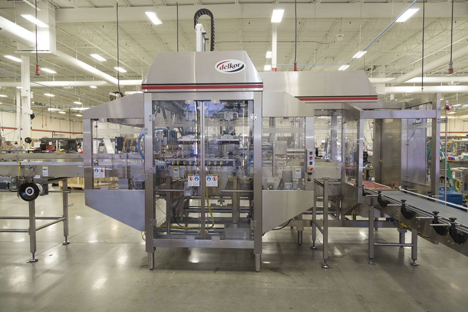 Flexible case packer with a more compact footprint